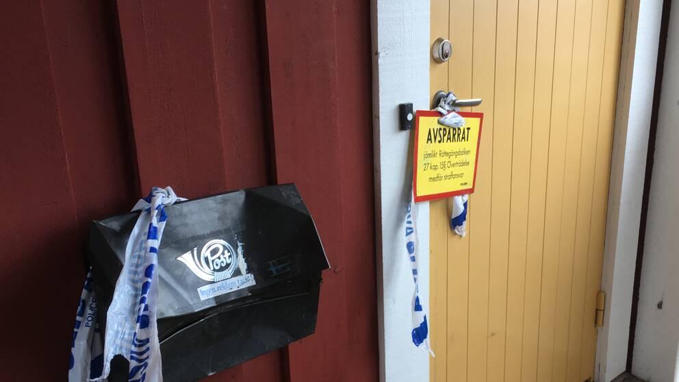polistejp på en brevlåda vid en avspärrad dörr