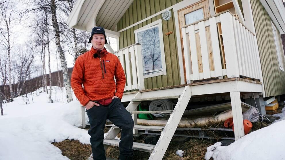 en ung man står framför ett litet trähus i fjällen, snö och gles skog