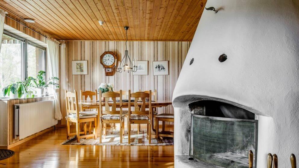 Interiörbild i en bostad. Kamin, matbord och stolar.