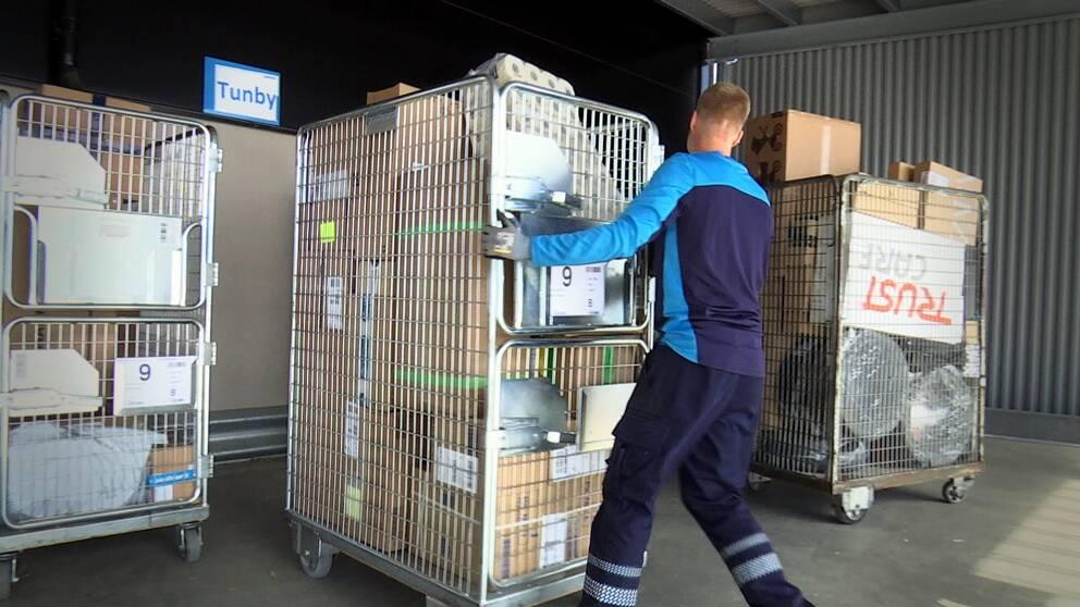En man rullar en vagn full med postpaket. Bredvid står likande vagnar.