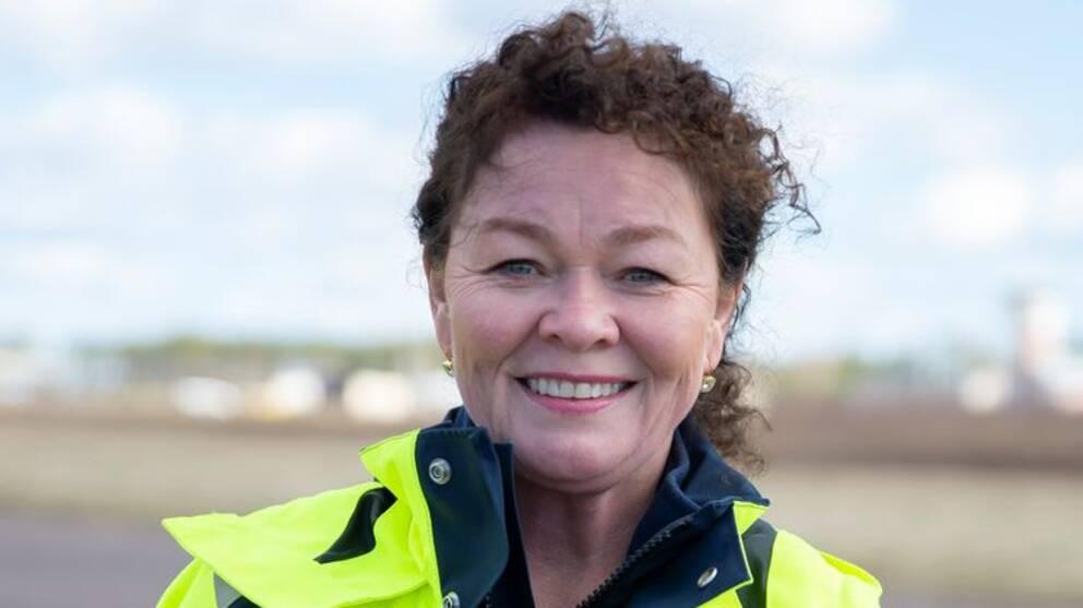 Camilla Sperling i en ljusgul jacka med Karlstad airports logotyp.