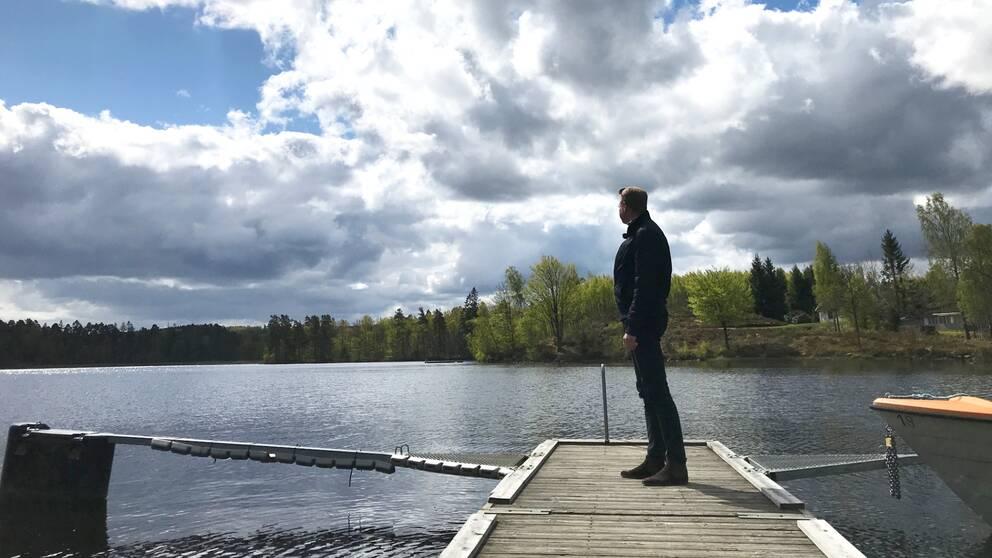 Krister Persson, näringslivs- och turistchef Örkeljunga kommun står på en brygga och tittar ut över en insjö.