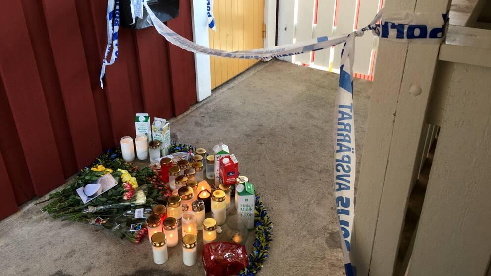 Blommor och lyktor utanför ett mordoffers dörr. Polisavspärrningar kring dörrren.