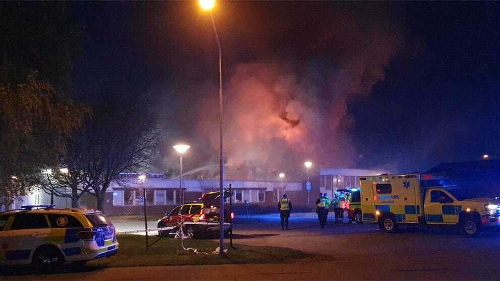 Ambulans och polisbil syns utanför en skolbyggnad. Det ryker kraftigt från byggnaden.