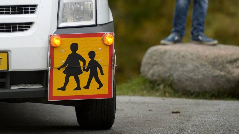 närbild på skylt på en skolskjuts-bil, i bakgrunden syns fötterna på en pojke som står på en sten