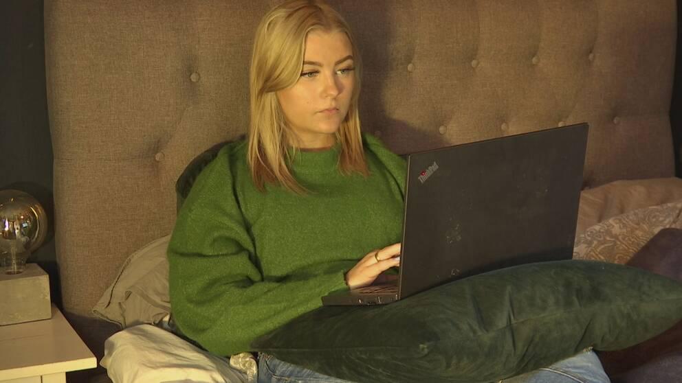 Gymnasieelev sköter skolarbetet hemma i sängen efter att distansundervisning införts i gymnasieskolorna.