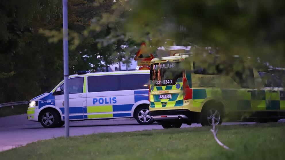 Polis och ambulans innanför avspärrningarna vid radhusområdet i Alby i Botkyrka kommun.