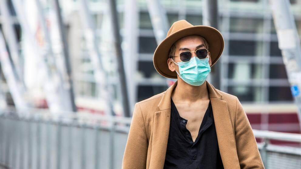 En man med munskydd går i vårsolen i Oslo.