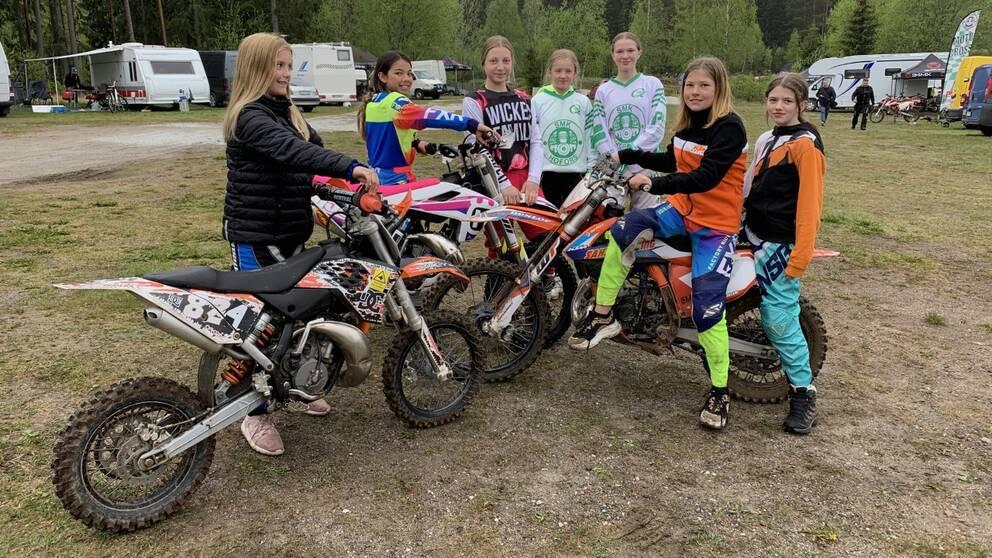 Sju tjejer står uppradade vid tre motocrosshojar på en gräsplan. I bakgrunden syns flera husvagnar och bilar.