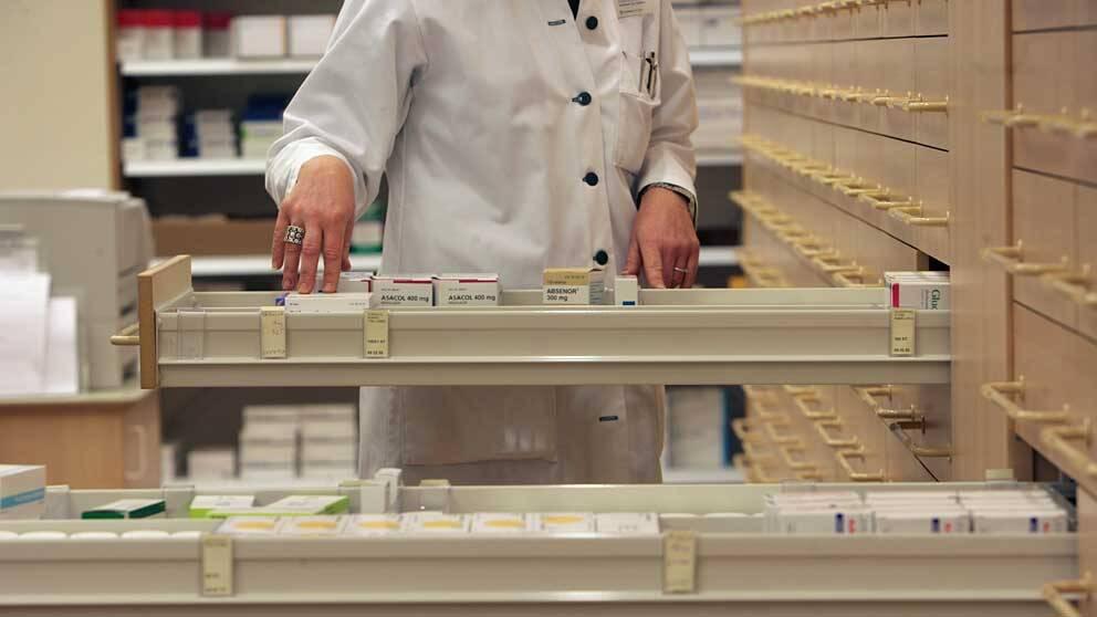 En apotekare letar efter receptbelagd medicin i en låda på ett apotek.