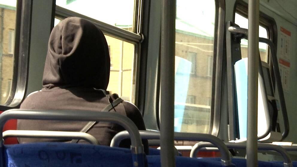 Kvinna på buss med luva.