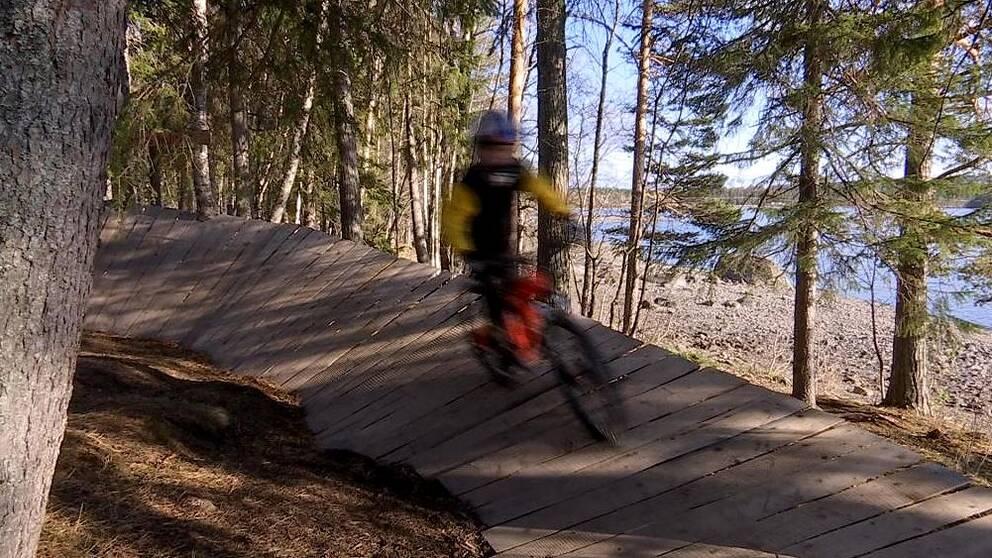 cyklist i farten i en velodromkurva av träplankor i skogen, strand i bakgrunden