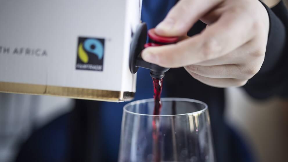 En hand som trycker fram vin ur en box.