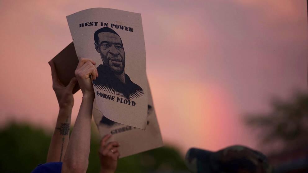 En demonstrant i Minneapolis håller upp en skylt med bild på George Floyd.