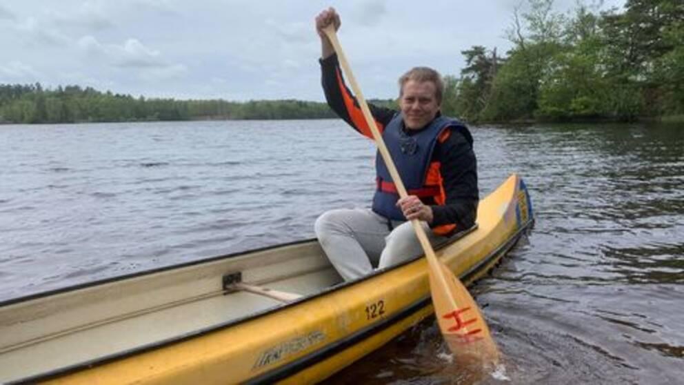 Kille sitter i kanot och ror med åra