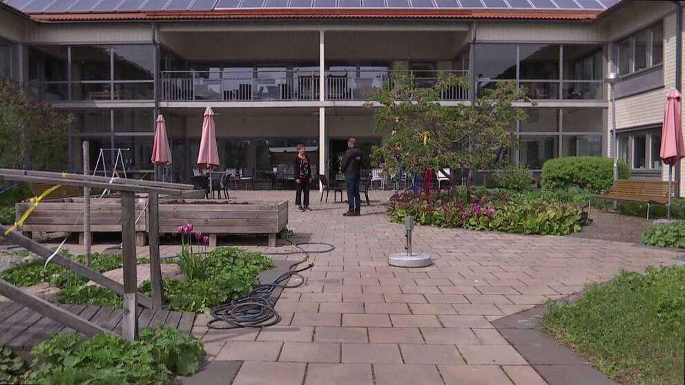 exteriör innergården på tvåplansbyggnad, äldreboendet Kungsljuset, en reporter intervjuar en kvinna