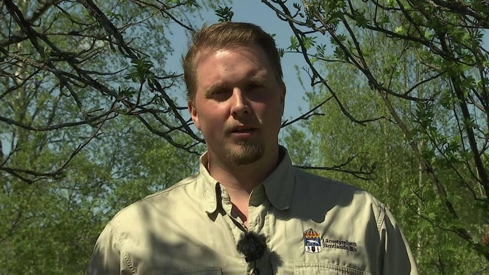 """Blond korthårig man utomhus, med beige skjorta med texten """"Länsstyrelsen Jämtlands län"""" på."""
