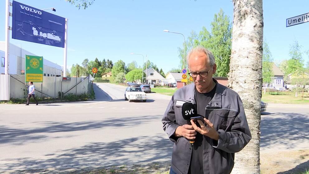Jan-Olov Carlsson, klubbordförande på Volvo lastvagnar, står utanför Volvo i Umeå och läser på en smartphone.