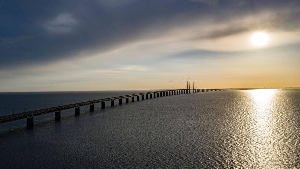 Svenskar som har fast bostad i Sverige får resa via Danmark vidare ut i världen på semester, enligt de danska reglerna. Öresundsbron i skymningen.