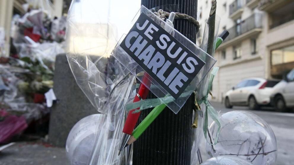 Blommor och pennor upphängda utanför Charlie Hebdos redaktion efter attentatet.