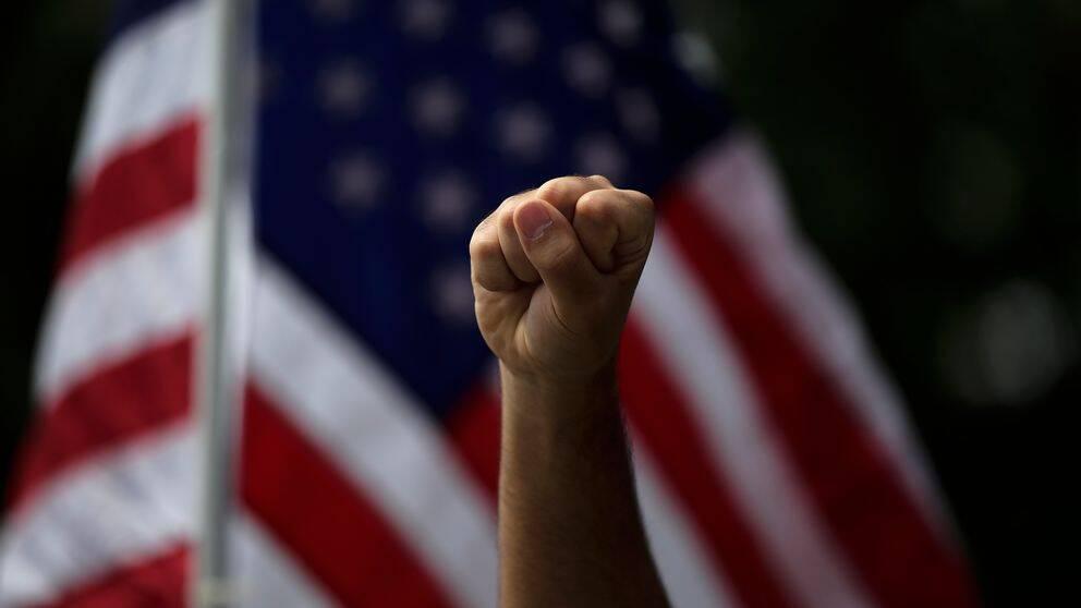 En person höjer knytnäven under en protest i Anaheim, USA över George Floyds död.