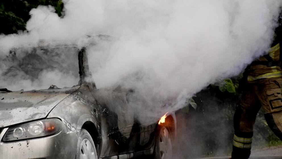 Brinnande bil och brandman