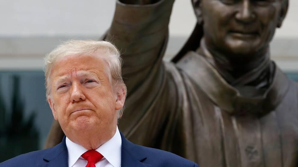 Donald Trump när han poserade framför statyn över påven Johannes Paulus II i tisdags.