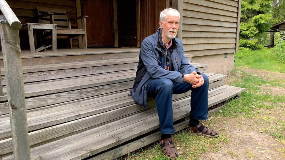 Äldre man med vitt hår och skägg sitter på en farstutrapp.