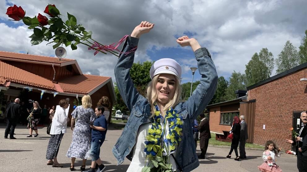 Marie Blomlie med vit studentmössa och ett fång rosor som flyger i luften.