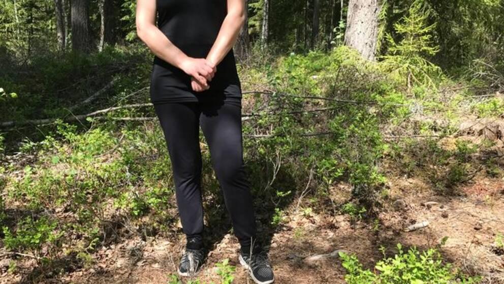 Anonym kvinna står i en skog.