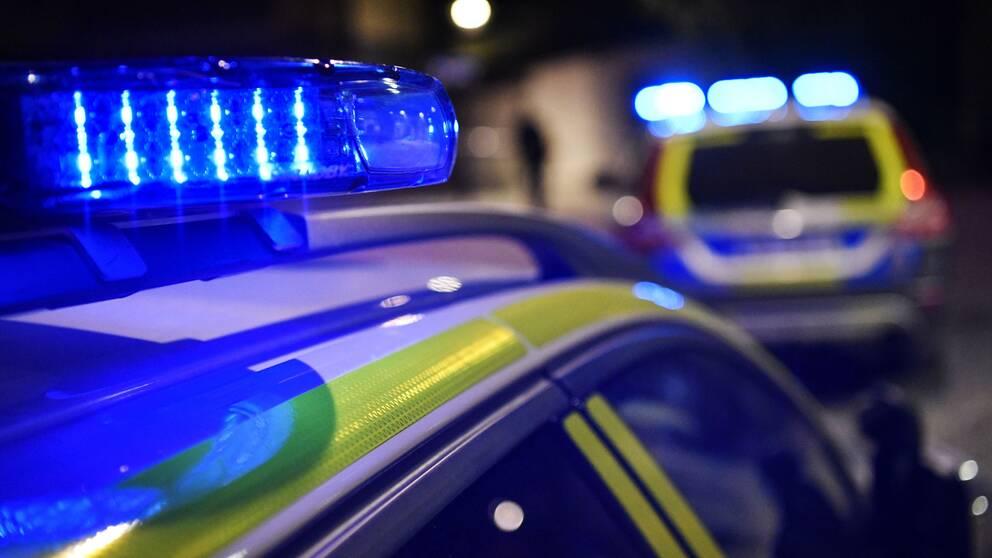 Nattbild på två polisbilars tak och blåljus.