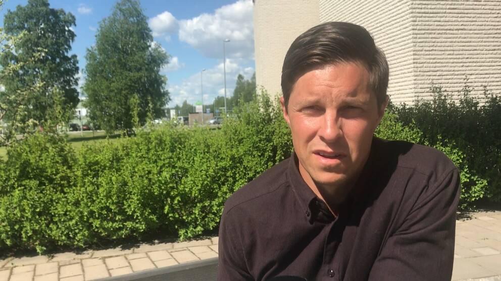 Regionschef för Företagarna i Västerbotten Jonas Nordin i svart skjorta intervjuad utomhus med buskar och husvägg i bakgrunden.