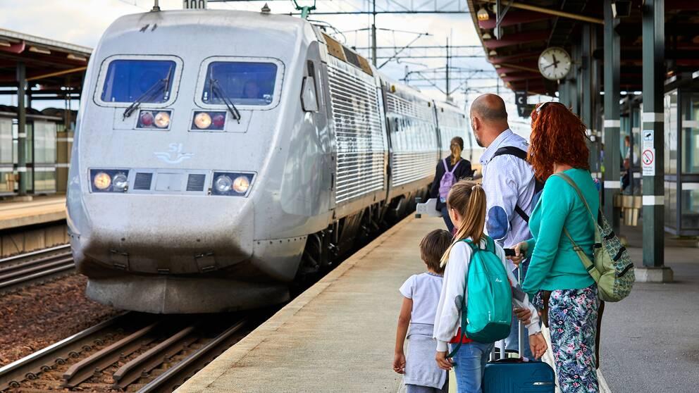 En familj inväntar ett inkommande tåg.