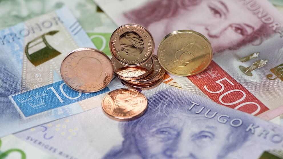 Närbild på svenska sedlar och mynt.