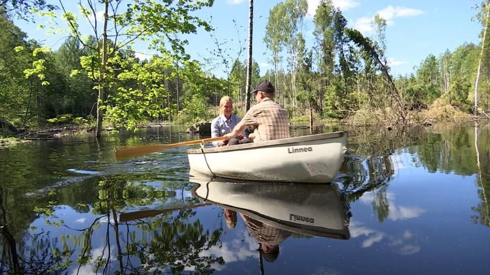 Två personer i liten roddbåt i en våtmark