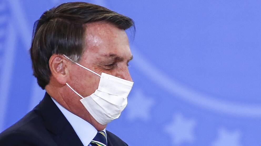 Närbild på Brasiliens president Bolsonaro i profil, iförd ansiktsmask under en formell tillställning.