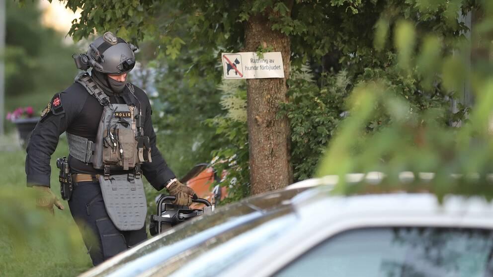 En polis med hjälm och skottsäker väst syns intill ett träd.