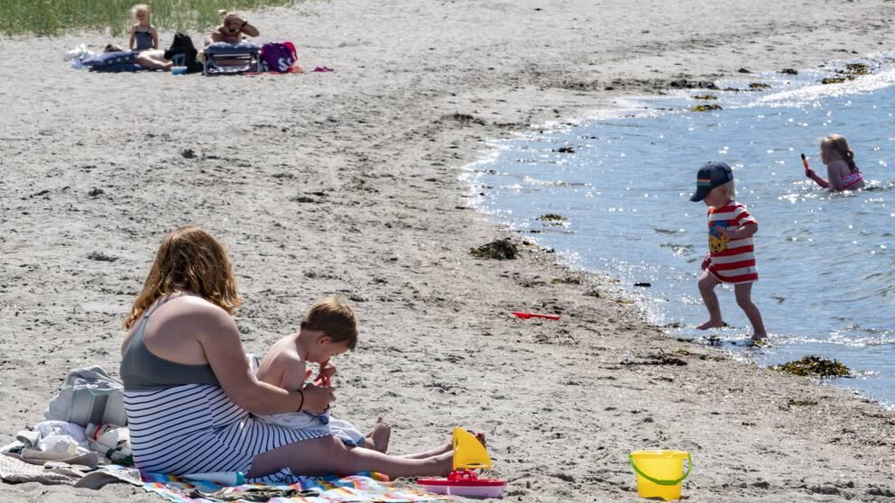 Vuxna och barn på en badstrand. Några badar, några sitter i sanden.