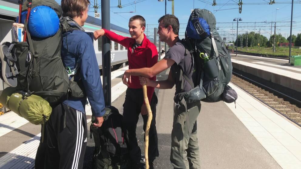 tre killar med ryggsäck utanför tåg på perrong