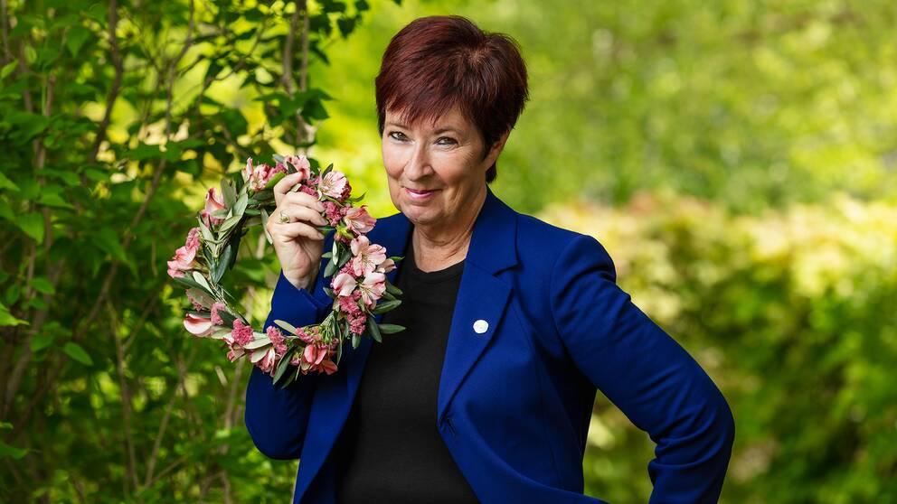 Mona Sahlin är tisdagens sommarvärld i Sommar i P1 på Sveriges Radio. Här står hon i sommargrönska och håller en blomsterkrans.