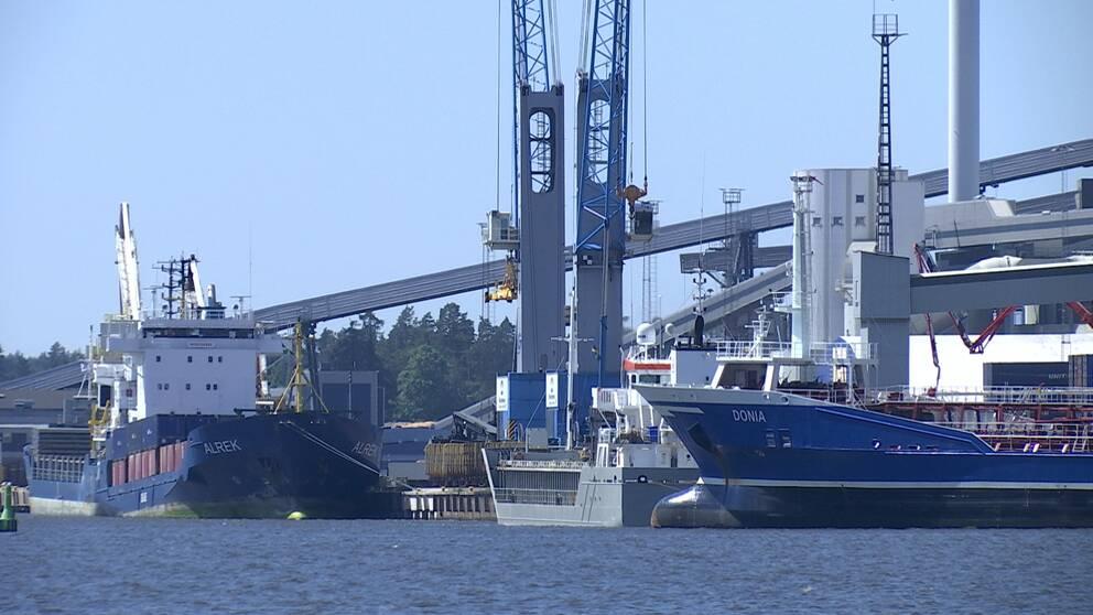 Två större fartyg ligger i vattnet intill en stor industri.