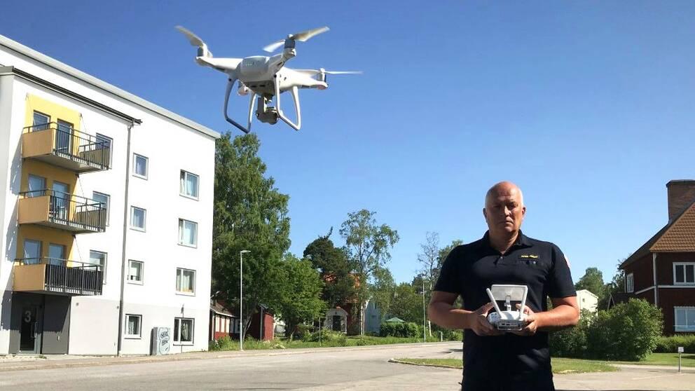 Ljusdals kommuns räddningschef Peter Nystedt har en handkontroll i händerna och en drönare flygandes bredvid sig.