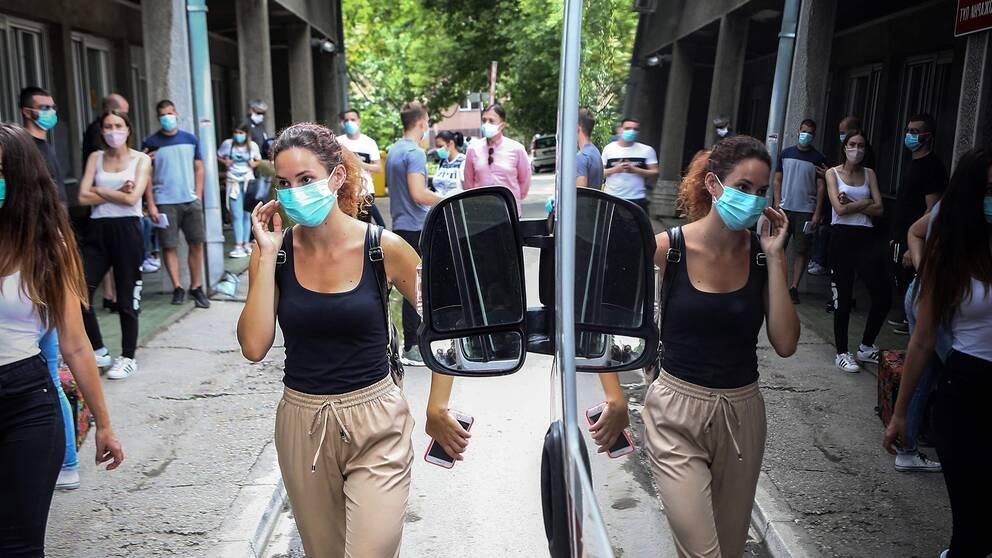 Flera personer med munskydd väntar utanför en klinik för att testas för covid-19.