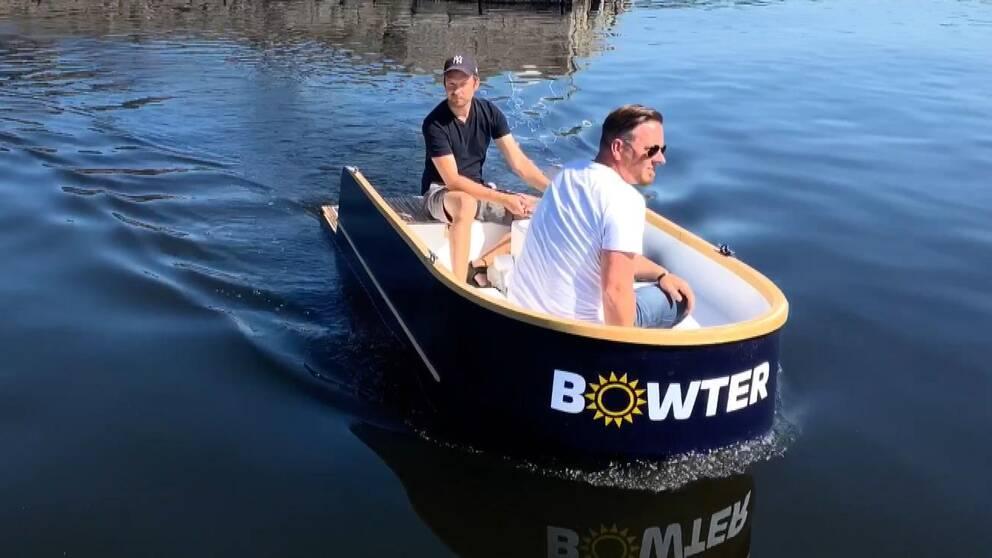 Två män sitter i en liten elbåt, en i fören och en styr i akten, på väg ut från en hamnpir i sten som syns i i bakgrunden.