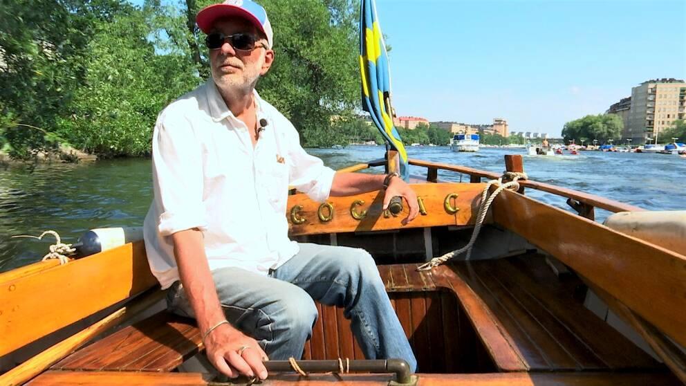 Christian Springfeldt sitter med en hand på rodret i sin träbåt Cognac.