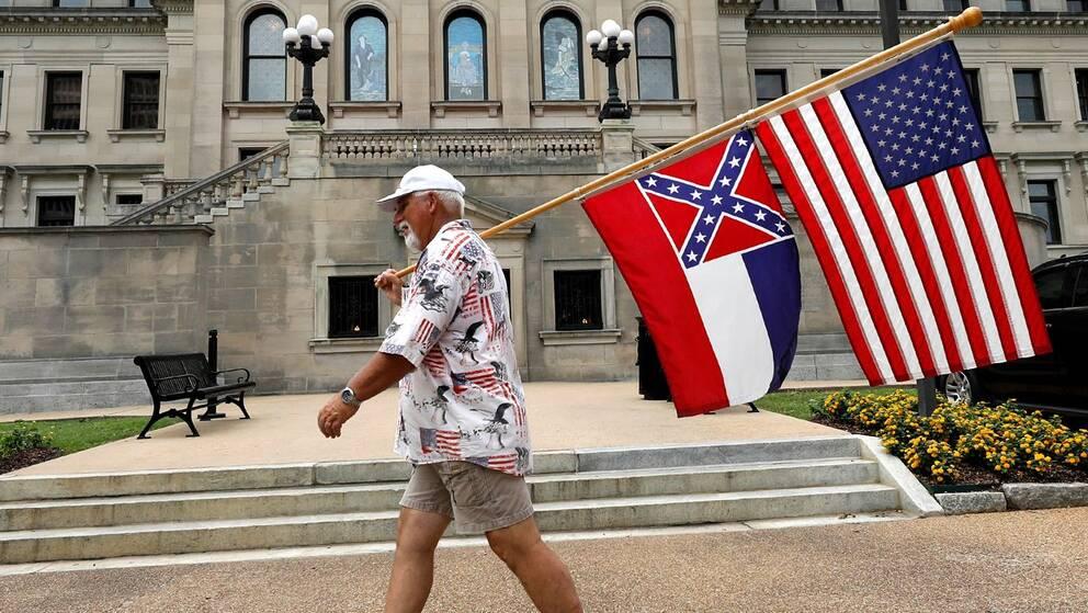 En man med den amerikanska flaggan och Mississippis nuvarande flagga med sydstatssymbolen.