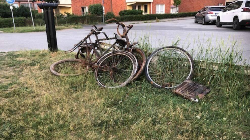 Rostiga cyklar står lutade mot ett räcke.