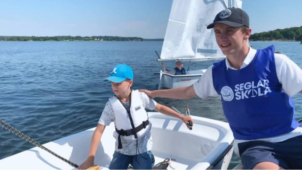 två killar i keps, en lite yngre och en äldre vid segelbåt