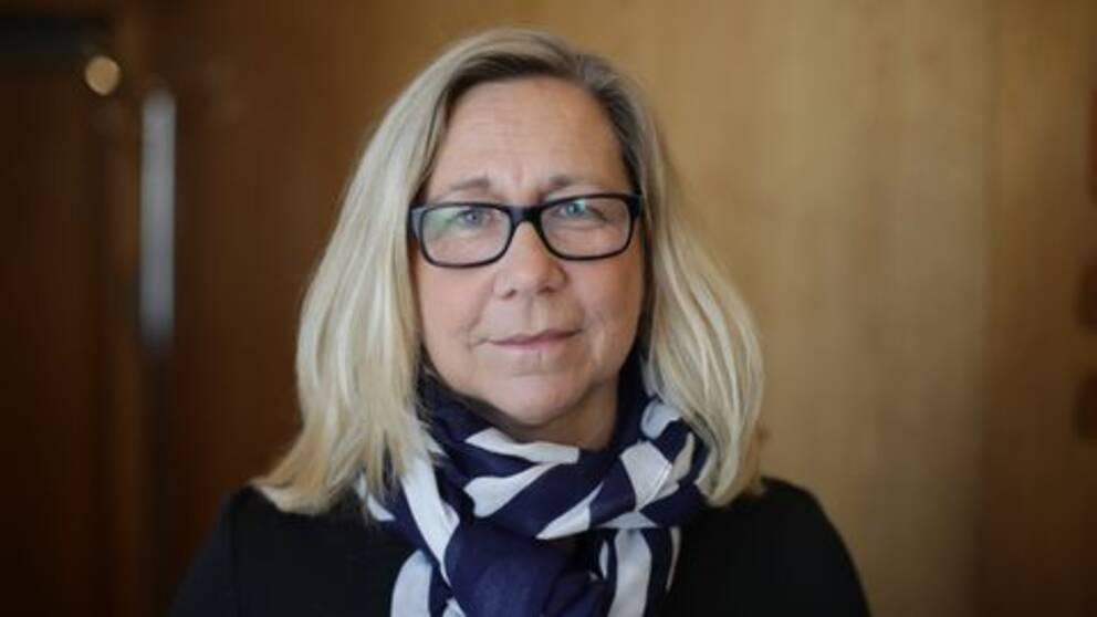 Blond kvinna i svarta glasögon och mönstrad scarf.