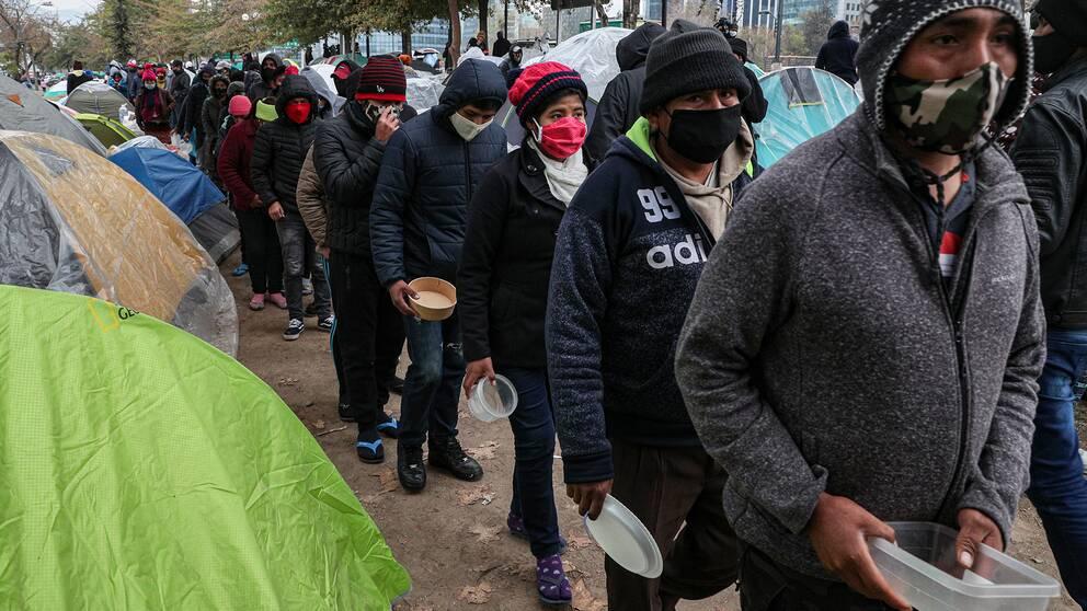 Fattiga migranter med munskydd och tomma matkärl i händerna köar utanför Bolivias ambassad i Santiago, Chile.